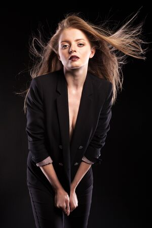 blowed: Beautiful fashionable woman with blowed hair on black background in studio photo. Glamour and elegance