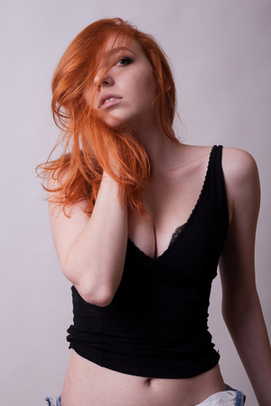 Sensual busty hot redhead woman in studio photo on gray background. Sexuality and sensuality. Attractive model