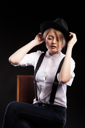 reggicalze: Gorgeous blonde model with suspenders and white shirt wearing a hat on black background in studio photo