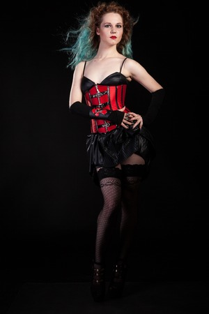 Sexy woman in red leather corset on black background in studio photo. BDSM and dominatrix Banco de Imagens