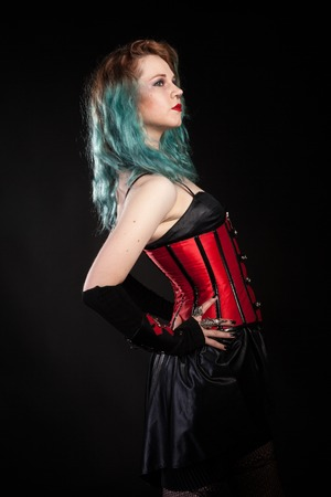 Attractive woman in fetish red leather corset on black background in studio photo. BDSM and dominatrix Stock Photo