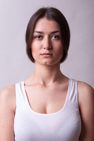 白いシャツを着ている美しい女性の肖像画。セクシーな女性。スタジオでの模型実験でポーズ完璧な美しい魅力的な女性