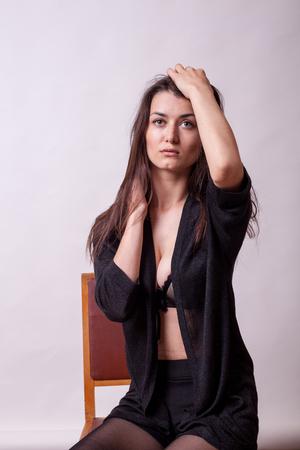 灰色の背景にファッション スタイルでポーズのセクシーな巨乳女性。セクシーな女性。スタジオでの模型実験でポーズ完璧な美しい魅力的な女性 写真素材