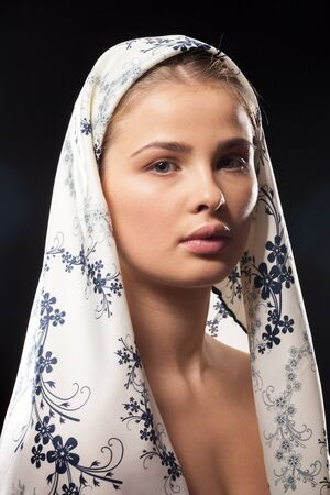 Gorgeous woman wearing a headscarf on black background in studio photo