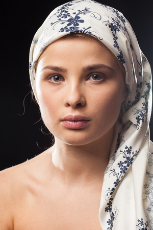 Portrait of young woman wearing a headscarf on black background in studio photo Stock Photo