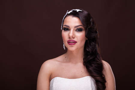 hacer el amor: Romantic bride with professional hairstyle and make up on brown background in studio photo. Bridal make up and hairstyle. Fashion and elegance