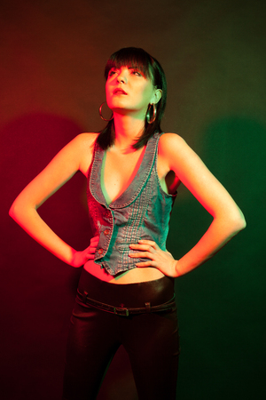 Brunette in leather pants in red and green light. Studio photo. Beauty and fashion