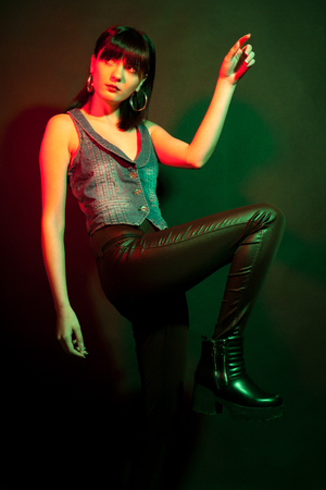 Glamour brunette in leather pants in red and green light. Studio photo. Beauty and fashion Stock Photo