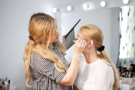 applied: Model is getting makeup applied by professional. Make-up presentation Stock Photo