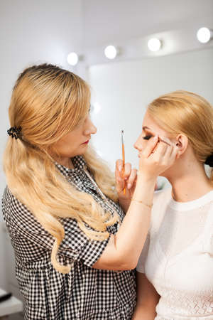 applied: Model is getting makeup applied by professional. Beauty industry. Fashion