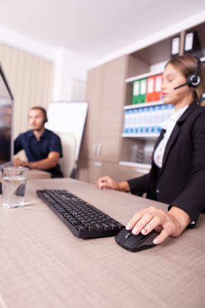 customer service representative: Man and woman working at customer service help line. Wearing headphones