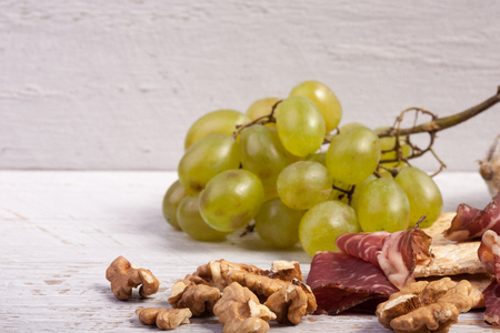 Antipasto appetizer on white wooden background. Healthy lunch