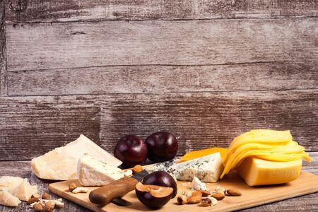Gourmet cheese apetizer on wooden background. Delicatessen snack