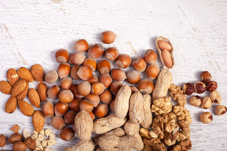 Mix of variety of nuts on white wooden background. Healthy raw snaks Stock Photo