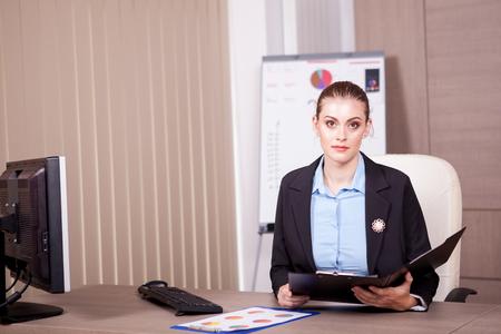 information analysis: Businesswoman with a chart folder in hands in her office