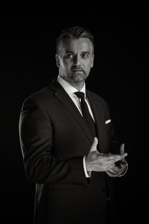 Porträt des erwachsenen überzeugten Geschäftsmannes im Studiofoto auf schwarzem Hintergrund in der schwarzen in einem weißen
