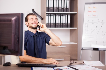 Smiling CEO in blue shirt and tie talking on the phone. Portrait of successful entrepreneur in his modern office. Happy young corporate worker at his job