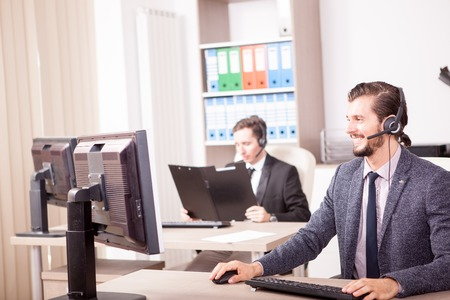 customer service representative: Two men from Customer service support working in office. Professional online and telephone assistant support