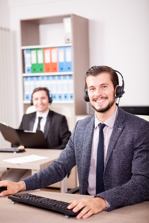 Two men from Customer service support working in office. Professional online and telephone assistant support