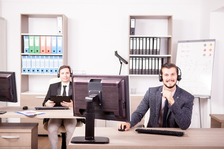 customer service representative: Smiling man working at Customer service support in the office. Professional online and telephone assistant support