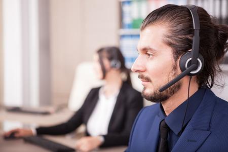 Portret van de mens van klantenondersteuningslijn in het bureau en zijn collega vaag op de achtergrond. Helpdesk en ondersteuning Stockfoto