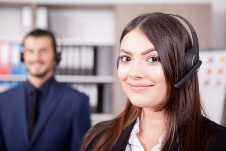 hotline: Woman working at the customer support and her colleague blurred in background. Help desk and support