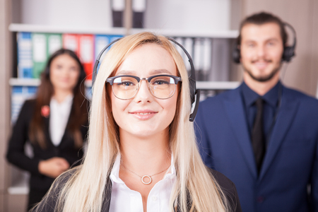hotline: Portrait of beautiful blonde from customer support line next to two colleagues
