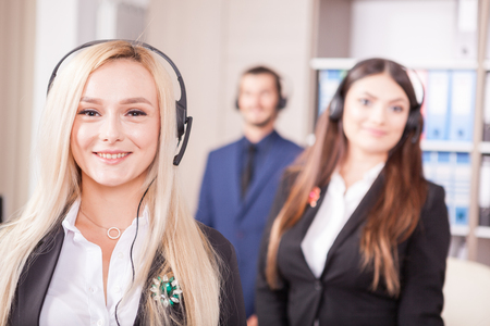 hotline: Portrait of customer support line worker next to two colleagues Stock Photo