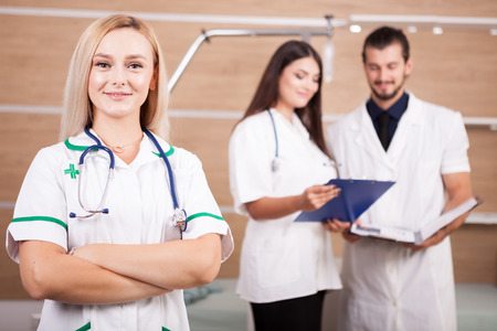 Portrait of confident doctor medical team with a blonde medic in front in hospital room Stock Photo