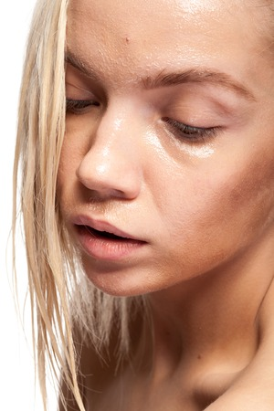 Gorgeous woman with wet face. Studio photo. Beauty and skin care