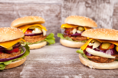Tasty burgers on wooden background. Fast and tasty food Stock Photo