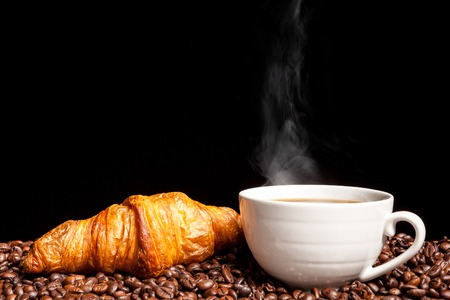 Chicchi di caffè del vapore e del croissant nella fine sulla foto. Buongiorno bevanda e snack
