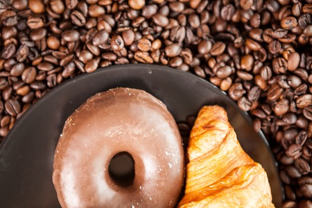 Coffee beans, donut and a cup of coffee in close up photo