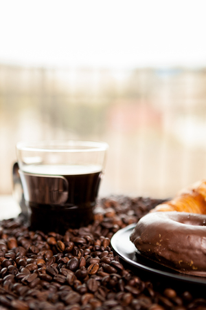 Croissant and coffee beans in close up photo. Delicious morning drink and snack