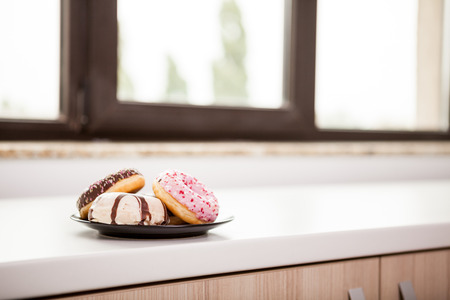 shop window: Plate with donuts next to window sill. Delicious junck food Stock Photo