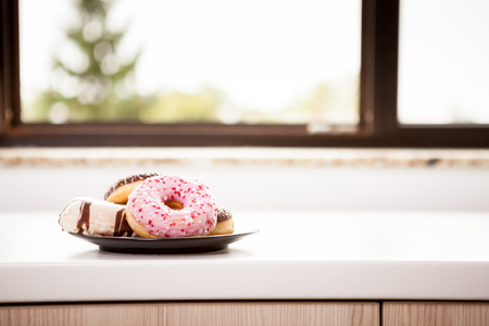 shop window: Close up of Plate with donuts next to window sill. Delicious junck food Stock Photo
