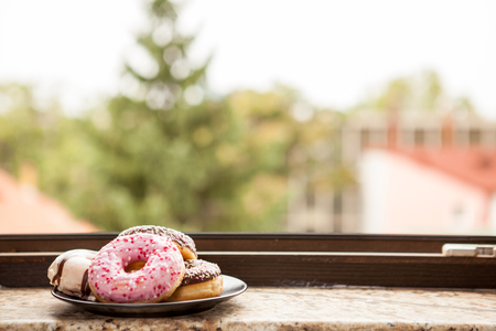 Plate with donuts next to window sill. Delicious junck food Imagens