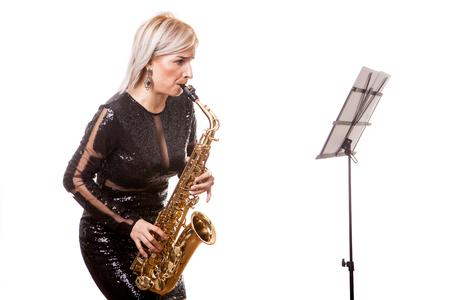 豪華なサクスホーン奏者女性彼女の楽器で演奏します。スタジオ写真で白い背景に分離 写真素材