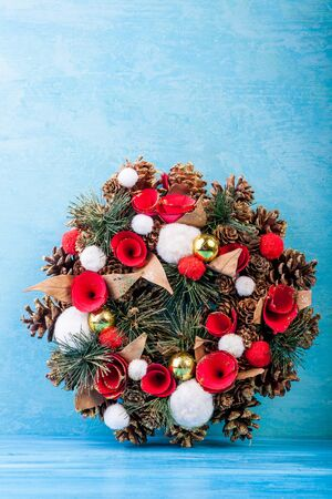 pine wreaths: Christmas wreath on blue wooden background in studio photo Stock Photo