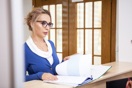 Business lady in the waiting area with paperwork ready for secretary Stock Photo