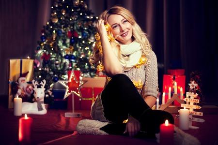 Hermosa mujer rubia sentada en la flor con un árbol de Navidad en el fondo y ella está sosteniendo algunas guirnaldas en las manos. Tarjeta de feliz Navidad Foto de archivo - 90332043
