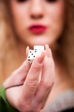 Close up of woman holding dice in hands. Conceptul winning image. The girl portrait is out of focus