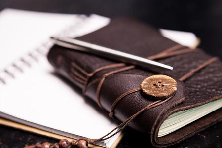 Ntoebook vintage rivestito in pelle su un diario aperto su una tavola di legno scura