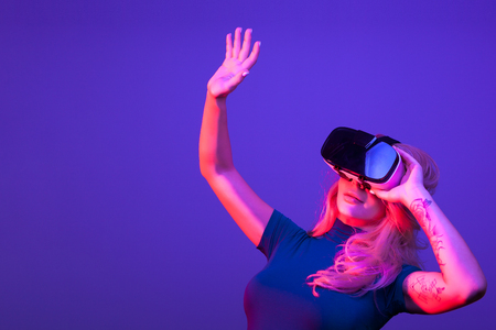Woman holding her hand up while wearing VR headset. Studio photo with multile colored lights and blue background Stock Photo