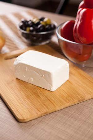 Feta chees on wooden board on a table next to a glass bowl of sweet red pepper and olives
