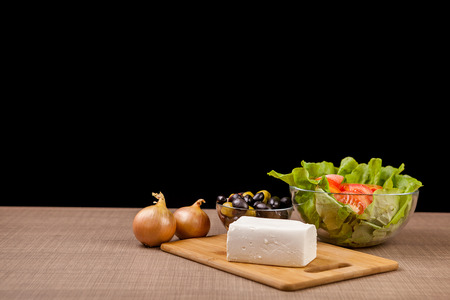 Fresh antipasto from feta cheese, onions and two glass bowls with fresh salad and olives on black background