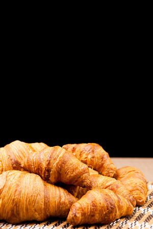 Freshly baked croissants lying on a table over a black background Zdjęcie Seryjne
