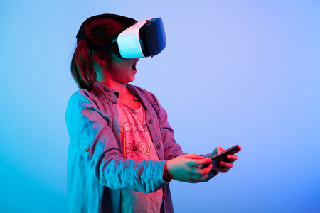 Surprised young girl playing virtual game with a VR headset on