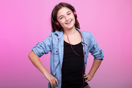 Smiling young teenager girl listening to music on pink background in studio photo