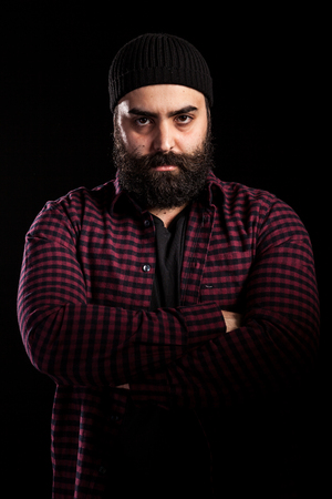 Portrait of angry bearded man on black background Stock Photo